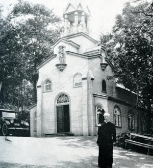 St Andre in front of the original Chapel to St Joseph
