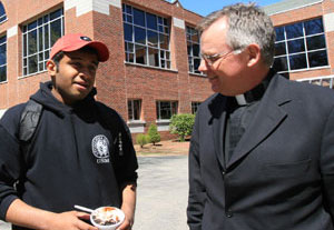 Rev John Denning, CSC, with a student at Stonehill College