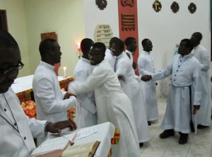 Congregation members extend a sign of peace and congratulations to the new novices