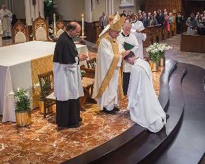 Bishop Rhoades lays hands on Pat Reidy in the Ordination Mass