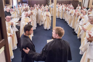 Holy Cross priests greet Matthew and Dennis in the sacristy after their Final Vows