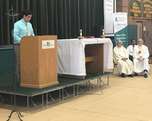 Colby McLiverty '16 addresses his fellow students at the end of Moreau Day Eucharistic Liturgy at Notre Dame High School, with seated to the right, Father Joseph A