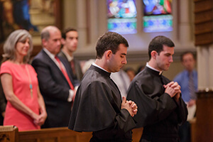 Ryan Pietroclaro, CSC, And Michael Palmer, CSC Pray For God's Blessing During Their Final Vows Mass