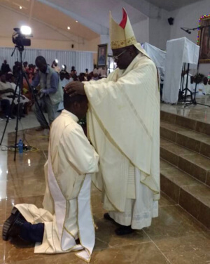 Bishop Yves-Marie Pean, CSC, lays hands on Deacon Sagesse during his priestly Ordination