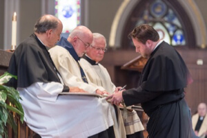 Chris Brennan, CSC, signs his vow formula after professing Final Vows