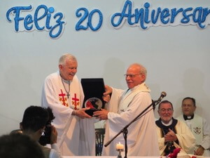 Fr Willy Raymond, CSC, presents an award to Fr David Farrell, CSC, for his leadership founding INFAM