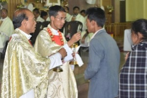 Newly Ordained Fr Bilingshar Syienlieh, CSC, gives communion