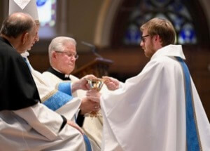 Newly ordained Fr Michael Thomas, CSC, receives the chalice and paten