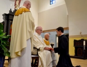 Fr William Lies, CSC, Provincial Superior, receives the First Vows of the 12 novices